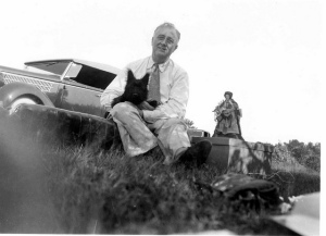 "FDR at a picnic on ""Sunset Hill"" near Pine Plains, NY. Fala is 4 months old. The doll next to the president is a handmade shaker doll made by Mary Garettson of Rhinebeck, NY. August 8, 1940"